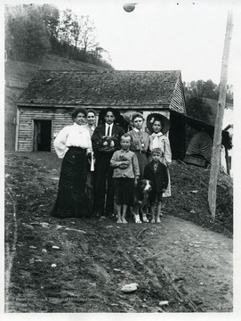 A family and their dog are standing in front of a house in Helvetia, West Virginia.