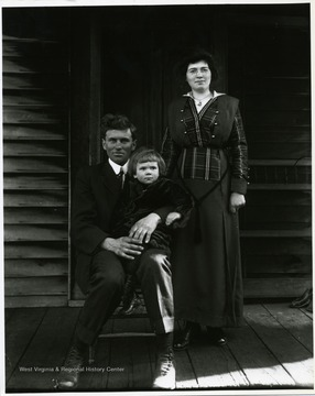 A father is holding his child and his wife is standing next to him on the front porch of their home in Helvetia, West Virginia.