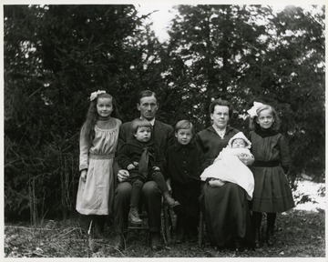 An unidentified family of seven seated outside for a portrait, Helvetia, West Virginia.