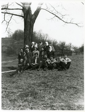 A group boys are sitting while a group of young ladies are standing in front of a tree in Helvetia, West Virginia.