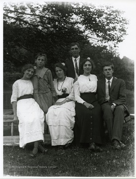 Two young gentlemen are posing with four ladies.