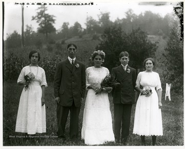 Two young gentlemen standing outside between three ladies who are holding flowers.