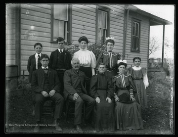 A group portrait of a family living in Helvetia, West Virginia. An elderly gentleman and a lady are sitting with three boys and four young ladies in front of a house.