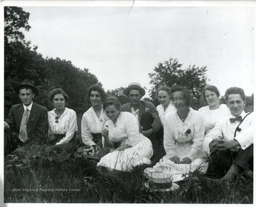 'Group sitting in field; hat on ground in front; Bertha Engler in front with flower.'