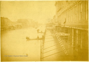 Men in canoes travel on Third Street in Huntington.