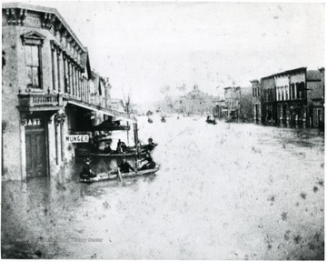 Men in canoes travel on Third St. after the flood.
