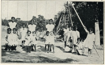 Children of the West Virginia Colored Orphan's Home in Huntington, West Virginia are playing on a swingset.