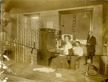 """Lewisburg Telephone Force"" includes woman telephone operator, wearing a head set while sitting at the switchboard and two other unidentified persons. Note the column of ""ringers"" or bells attached to the middle window frame."