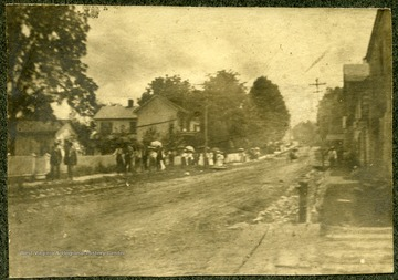 People walking on the sidewalk of Church Hill, Lewisburg, W. Va. 'just after the corner stone layed.'