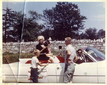 Jayne Mansfield, the Grand Marshall of Martinsburg Centennial Parade and her daughter ride in a car driven by Jim Dailey, sign autographs for two young boys.