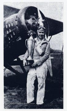 'Melba Gorby Beard with her plane, and the coveted Amelia Earhart Trophy, won at the 1935 National Air Races, Cleveland, Ohio. She still flies (in 1979) a similar plane to antique airplance events.'