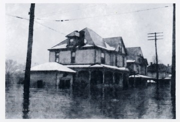 'One of the 1930-40's floods on Maple Avenue, New Martinsville, West Virginia. The Postlethwaite house and garage are in foreground, and 714 Maple Avenue is behind. The floodwaters are not on Postlethwaite pooch, but 714 porch and living area are covered. The McColloch family lived here at this time.'