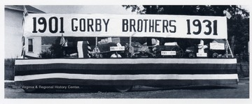 'Gorby Brothers Grocery parade float depicting delivery methods over the years. Shown are a wheelbarrow 1901-1903; horse and wagon 1903-1914; and truck 1914+. The float was built on the store truck.'