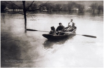 'Late 1940's flood picture taken from the porch of the Gorby home at 663 Maple Avenue, New Martinsville, W. Va.  Maple Avenue is 6-8 feet beneath the boat.  My sister Martha; Sam McColloch has the oars; and Aunt Mary Louise Gorby in the far end.  The rowboat belonged to the Gorby Bros. store.  It had many uses during the floods from delivering groceries, moving the store stock and furnishings, and taking us to the church to help move the church furniture.  When the work was finished, there was time to row around town and explore where everything familiar was submerged.  Then later, the cleanup would begin.  It was a big adventure for the children but not for the adults.'