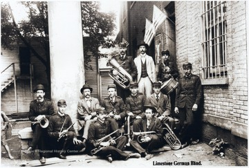 'The Limestone German Band, Posing at the Old Wetzel County Court House before 1900.  John Henry Gorby second from left with clarinet, Charles Thomas Gorby and George Ira Gorby with baritones in front of John Kaufman in light suit.  Other identified persons: John Kaufman in light suit in back.  Ed Frei seated right on ground.  'Limestone' is the ridge top at the head of Doolin Run about five miles east of New Martinsville.  Schools and churches attended by Doolin residents were located on 'Limestone' or the adjacent American Ridge.  Charles T. Gorby taught in the Limestone School.  William Gorby, grandfather of the Gorby brothers, was among the original members of the Limestone Church.  This Wetzel County Courthouse in this photograph faced south.  The present one built in 1900 is located on the same lots, but faces east and is made of stone. Photo from the collection of Pearl Frei.'