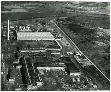 'An overall aerial view of Kaiser Aluminum's Ravenswood Works located on the Great Bend of the Ohio River, six miles south of Ravenswood and midway between Pittsburgh and Cincinnati.  Fabrication Plant is shown in the foreground, casting facility in the center and the Reduction Plant in the background near the 613 foot chimney.  On the main line of the B and O Railroad and West Virginia State Route 2, the Works is two days' delivery time from 50 of the nation's 100 largest cities and 70 percent of the aluminum consuming market.  Public Relations Dept.  Ravenswood Works.  Kaiser Aluminum and Chemical Corp. Ravenswood, W. Va.'
