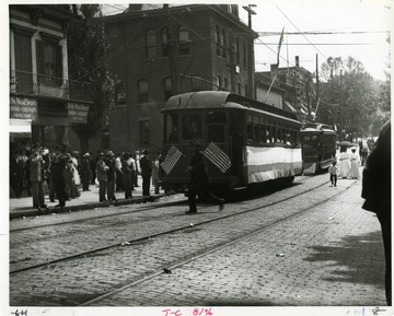 Townspeople are boarding street cars on High Street in Morgantown, West Virginia.