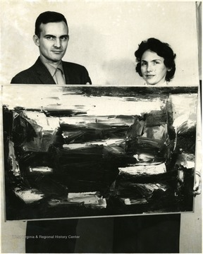A man and woman hold an abstract painting.