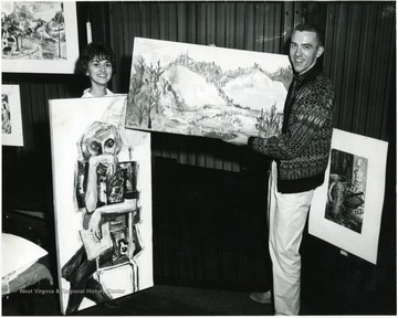 Two students display their paintings.