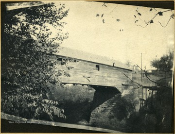 Covered bridge spanning Deckers Creek. Trees, telephone poles, and fence apparent. View of foundation of bridge.
