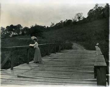 Woman standing on bridge spanning Falling Run. Pathway apparent on other side of bridge. Field leading to edge of trees.