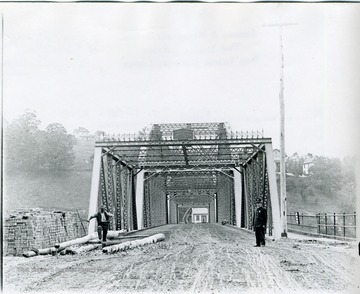 View of the bridge spanning the Monongahela River. Two men standing in front of bridge. One man wearing a suit and a badge. To the right of bridge is a pedestrian walkway.
