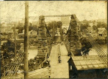 Workmen can be seen standing on bridge.