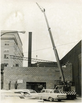 A crane works on placing a steel beam for a building in Morgantown.