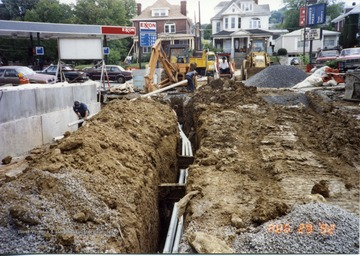 Workers can be seen constructing South Park bridge in Morgantown, W. Va. Running pipe throught trenches.