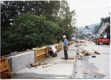 Construction in progress of South Park Bridge. Three workers can be seen on bridge.