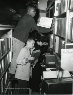 African-American boy climbs over top of another student to look at a book.