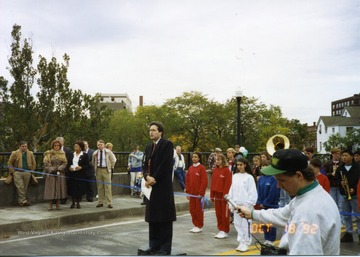 Speaker addressing public on New South Park bridge. Parade members can be seen behind speaker. Man holding microphone in lower right hand corner of picture.