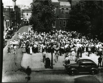 Crowd of people standing in the Courthouse Square.