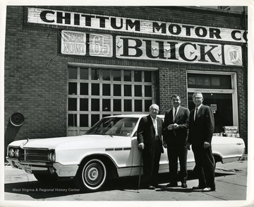 Three gentlemen are standing in front of a 1965 Buick at the Chittum Motor Company in Morgantown, West Virginia.