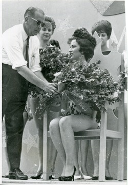 J. W. Ruby gives flowers to Miss Sterling Faucet at her coronation.