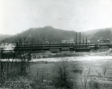 American Sheet and Tin Plate Company located in Sabraton, W. Va., near Morgantown, W. Va. Houses on the far side of the factory. Bare ground on near side of factory.