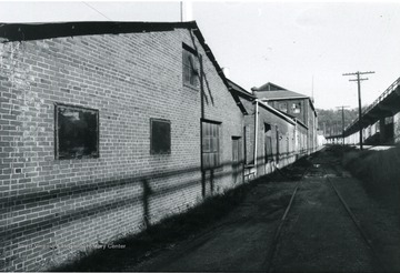 'View looking north along Rail road shows additions and original mill portions of east side of building.'