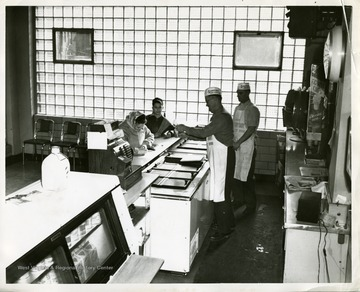 A mother and son purchase ice cream at the Sanitary Milk Bar in Morgantown, West Virginia. William Barker, foreground, and Emory Yauger are pictured.