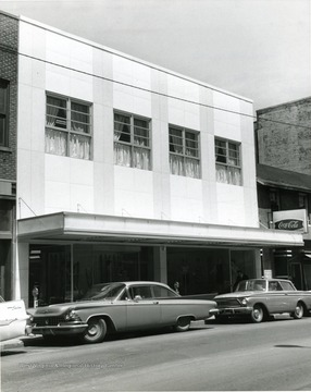 O. J. Morrison's shop in Morgantown, W. Va., after refacing exterior of building. Automobiles parked at meters along the street.