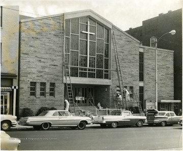 Men working on the windows and railings on the outside of the Baptist Church on High Street, Morgantown, W. Va.