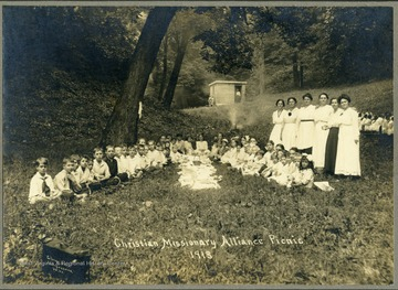 Group portrait of children attending picnic held by the Christian and Missionary Alliance Church. Children seen sitting around food. Women stand behind children on the right side of the group.