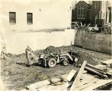 Men working on the new city library location, one is on a backhoe, Morgantown, W. Va.