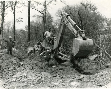 Man using a backhoe to dig in a wooded area while another man watches, Morgantown, W. Va.