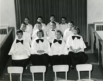 Children's Choir dressed in robes, setting in choir section. Choir at the Presbyterian Church located in Morgantown, W. Va.