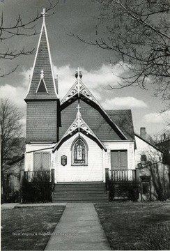 'Taken by Roy T. Emerson 1950 for Trinity Women's Auxiliary Yaar Book' Letter enclosed reads: ' July 1, 1959   To Whom it May Concern: Enclosed please find snapshot of Trinity Episcopal Church taken in 1950. This picture was used on  yearbook of Trinity Women's Auxiliary. In the year 1950. Trintiy was sold to a Church group, dismantled and moved board by board to their Church property near B--? W. Va. This over the forth or fifth move for this Church building. Trinity Church was purchased by first Vestry from the Baptist Church, before this time the Episcopal services were being read in old Rogers' home. The church stood at top of High Street before street was paved. With a great deal of effort it was finally moved to spot where New Farmers and Merchants Bank is now going up; however during move a rain storm hit and Church got bogged down in mud and stood in the middle of High Street for several weeks before ground was solid enough to prepare another attmept. The church was moved later, as shown in Post picture to spot next to Masonic temple and the place where Trinity Parking lot is now. This is the tale as told to me by Brad Laidley for most accurate account contact him. Sincerely, Monica Emerson, New Timer?'