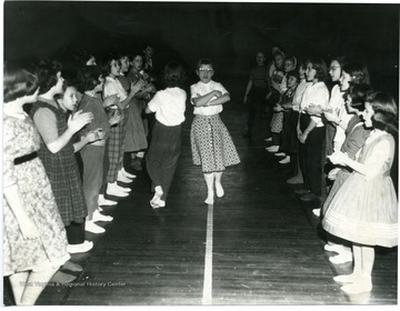 Kids dance the Virginia Reel in the gym.