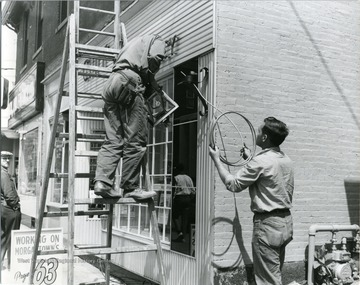 Workers seen running a light fixture on a building located on High Street in Morgantown, W. Va.