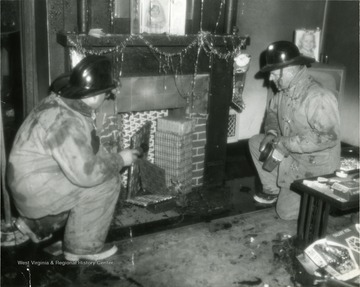 'Firemen in a residence extinguishing a fire'. Decorations imply it was Christmas time at the time of fire.