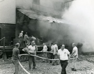 Men hold the water hose for the firefighters, as they try to extinguish a fire at the Davis-Lynch Glass Company in Star City, near Morgantown, W. Va.
