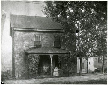 A woman sits on the porch of the Old Stone House.